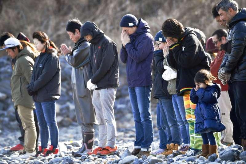 311東日本大地震七周年之際,人們在氣仙沼市的海邊爲亡者祈求冥福。(美聯社)