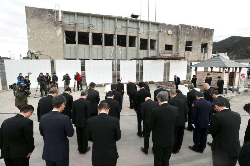 岩手縣大槌町的公務員在已經毀損不堪用的町役所前追悼七年前的慘痛回憶。(美聯社)