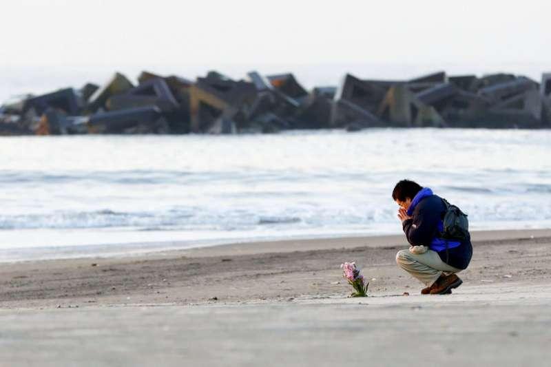 一位日本民眾在311東日本大地震七周年之際,在仙台市的荒濱海灘獨自插了一束花在沙地上悼念亡者。(資料照,美聯社)