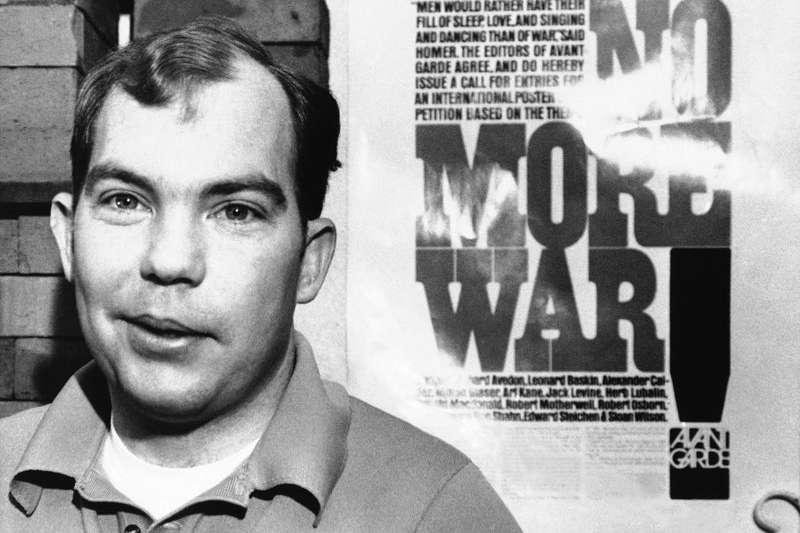 美萊村大屠殺50周年,美軍主使者凱利中尉,在接受軍法審判之前,曾在反戰海報前留影。(AP)