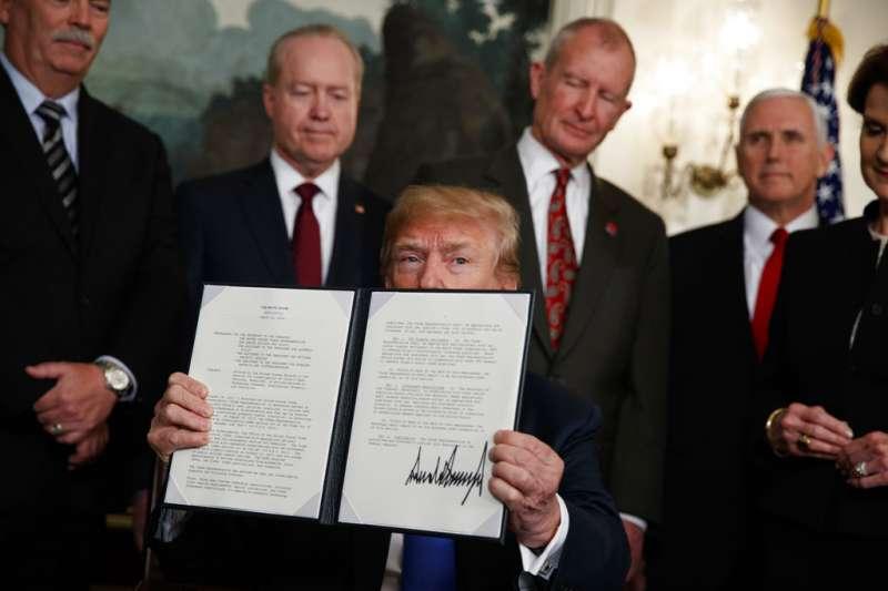川普展示他剛剛簽署的總統備忘錄,美國貿易代表辦公室15天之內將啟動對中國某些商品的關稅。(美聯社)