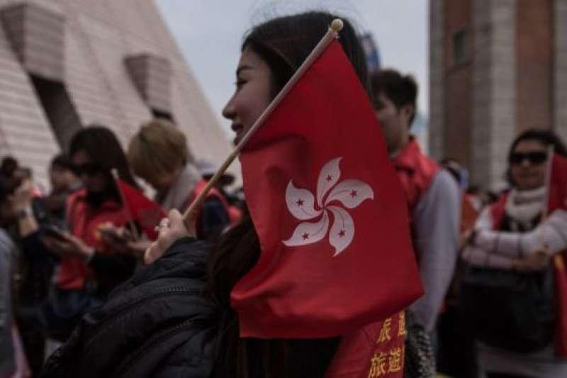 香港民眾手持特區區旗。(BBC中文網)