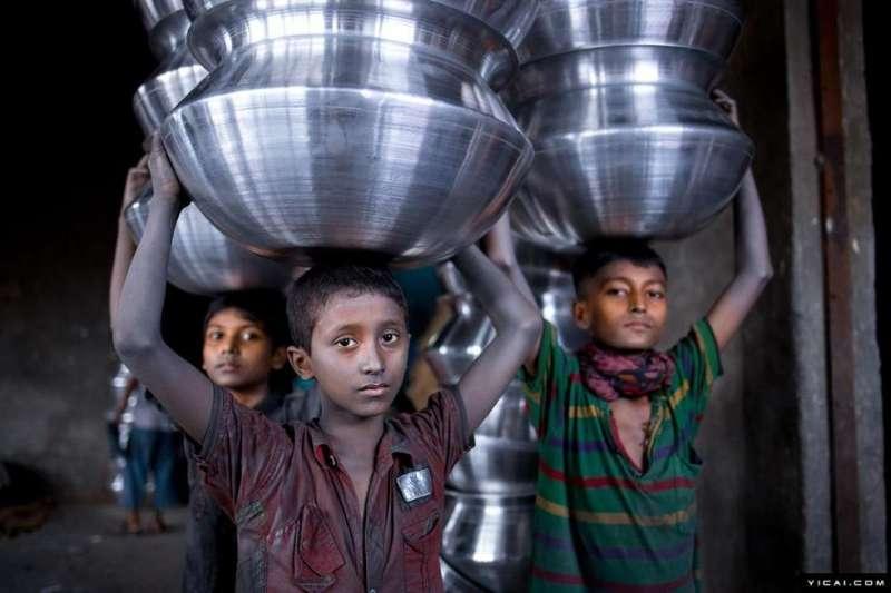 孟加拉國達卡,少年頭頂鋁製品。據報導,製做鍋罐的鋁工廠在孟加拉國十分盛行,然而在這些工廠裡有不少15歲不到的童工,粗略估計所佔比例達到一半。(圖/言人文化提供)
