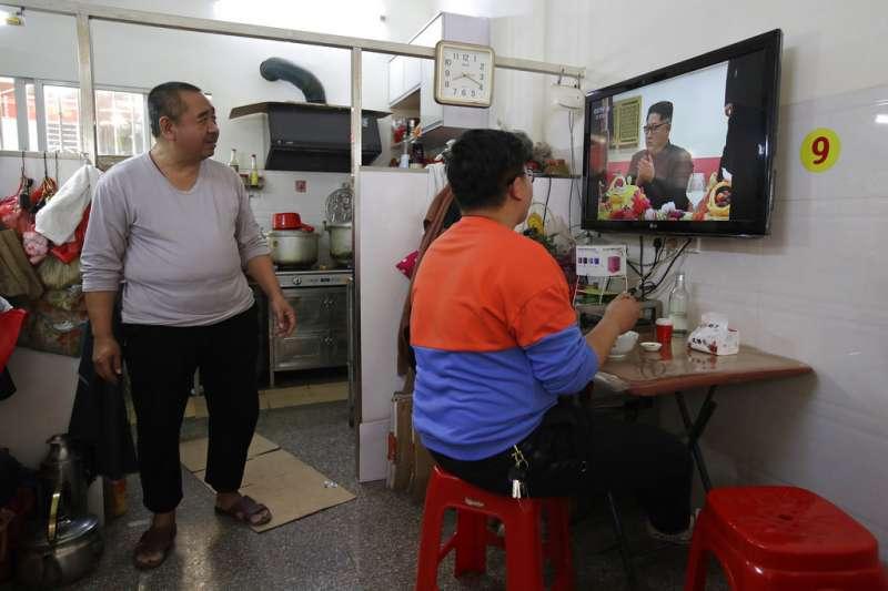 廣東民眾正在收看金正恩訪問北京的電視報導。(美聯社)