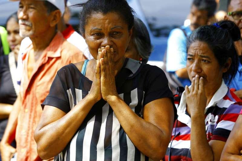 委內瑞拉警局拘留所28日爆發大火,造成68人死亡,囚犯家屬雙手合十,為家人祈禱。(AP)