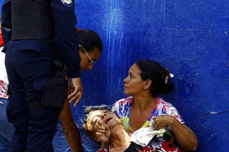 委內瑞拉警局拘留所28日爆發大火,造成68人死亡,囚犯家屬遭警察投擲的催淚瓦斯。(AP)