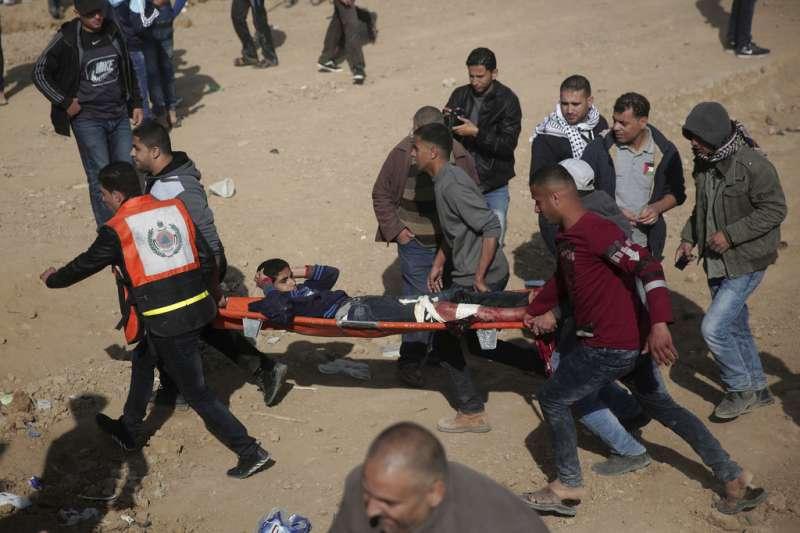 以色列軍隊30日與巴勒斯坦抗議民眾在邊境爆發衝突,造成至少16死,抗議民眾幫忙運送傷者。(AP)