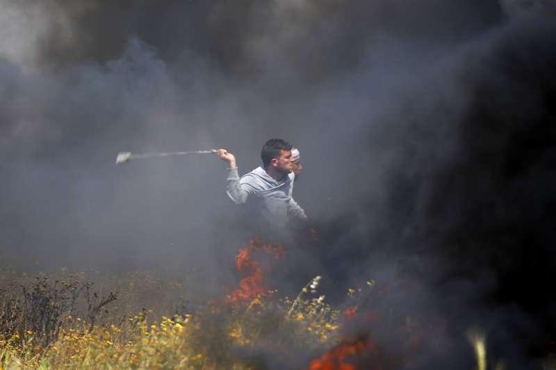 以色列軍隊30日與巴勒斯坦抗議民眾在邊境爆發衝突,造成至少16死。抗議民眾在煙霧中丟擲石頭。(AP)