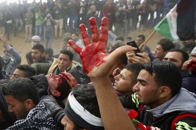以色列軍隊30日與巴勒斯坦抗議民眾在邊境爆發衝突,造成慘重死傷,抗議民眾幫忙運送傷者。(AP)