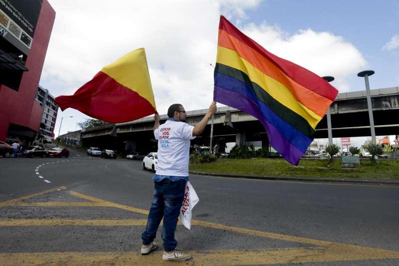 3月31日,奎沙達的支持者舉著「公民行動黨」的旗子與象徵同志平權運動的彩虹旗(美聯社)