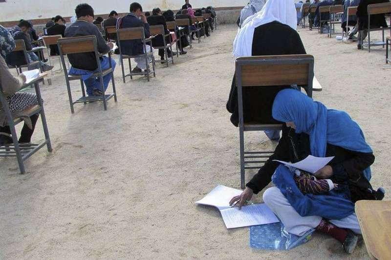 阿富汗小學老師阿瑪迪3月16日帶著孩子坐地應試的相片感動世人,讓她成功完成上大學的夢想。(AP)