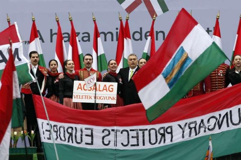 中歐國家近來偏向極右派民粹主義、反移民立場。圖為匈牙利總理奧爾班(中間穿西裝者)3月15日與穿著傳統服飾的表演者在國會外合唱。(AP).jpeg