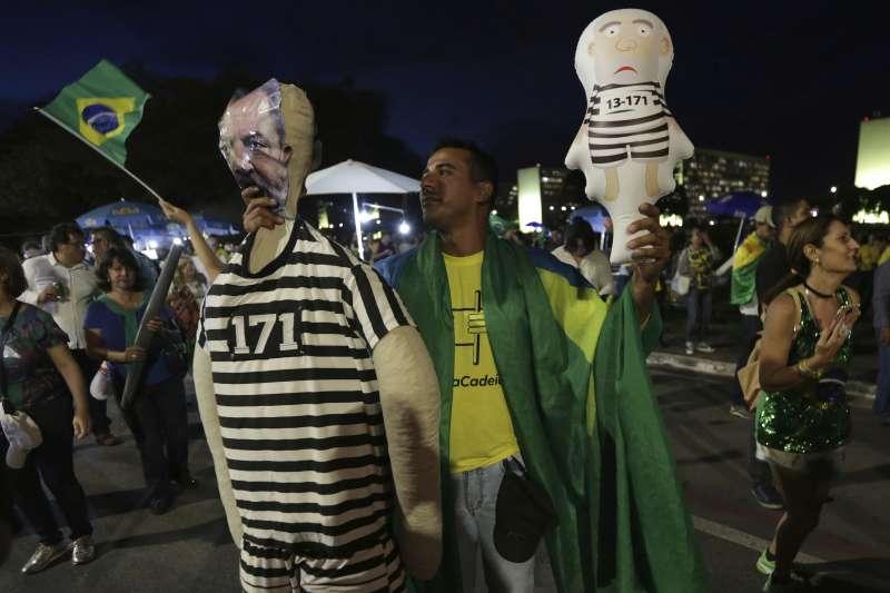魯拉反對者手拿穿著囚衣的魯拉玩偶,希望最高法院維持一審判決,將魯拉送進大牢。(美聯社)