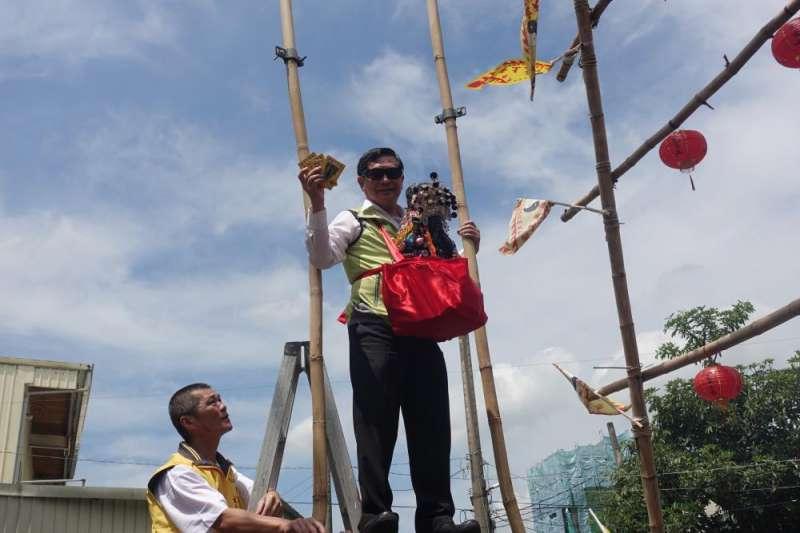 107年嘉義市鞦韆節即將登場,嘉義市長涂醒哲背著玄天上帝神像,站上12公尺高的鞦韆,撒招財錢母給民眾,邀請全國鄉親屆時來嘉義高空大挑戰。(圖/嘉義市政府提供)