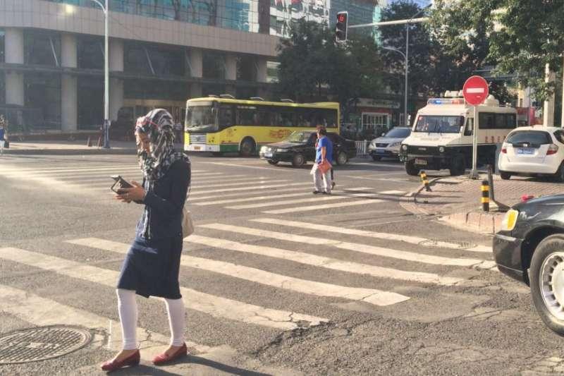 烏魯木齊街頭有婦女邊走邊看手機。(美國之音)