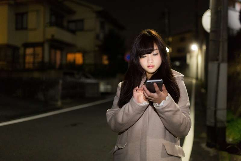夜晚街頭,手機不離身的人。(圖/@pakutaso)