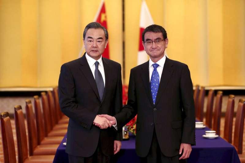 中國外交部長王毅訪問日本,與日本外務大臣河野太郎合影。(美聯社)