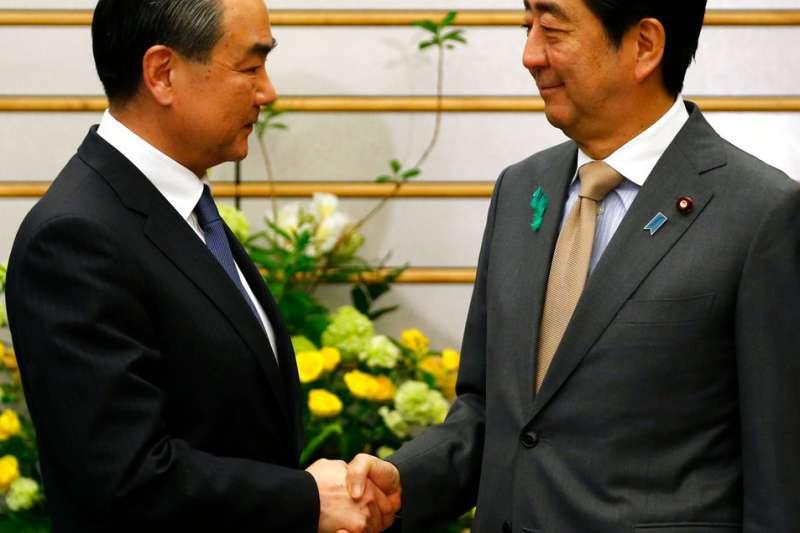 中國外交部長王毅訪問日本,與日本首相安倍晉三握手致意。(美聯社)