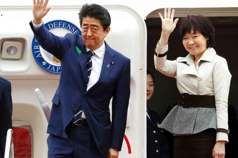 日本首相安倍晉三(左)與夫人安倍昭惠(右)17日登上專機前與媒體揮手,準備訪問美國,會見川普。(AP)