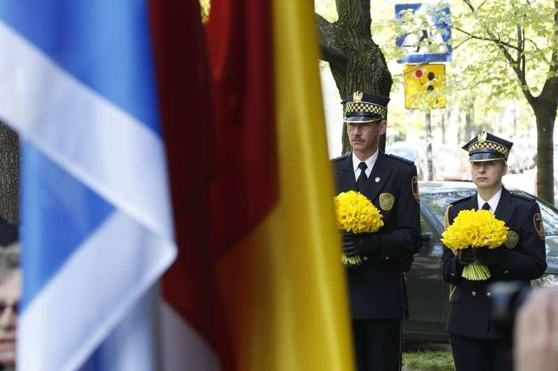 2018年4月19日,波蘭舉行華沙猶太區抗暴75周年紀念儀式,警察手捧水仙花,悼念罹難者。(AP)