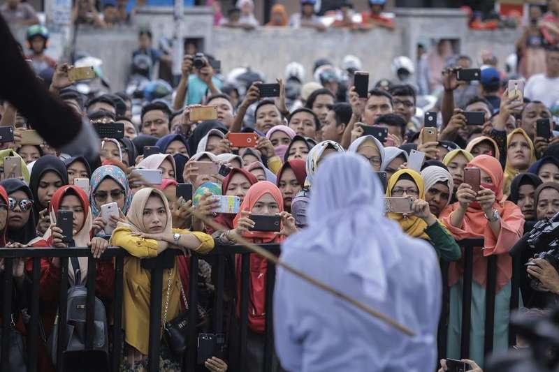 印尼亞齊特區(Aceh)奉行嚴格伊斯蘭律法(Shariah law),酗酒、賭博、亂塗鴉皆為違法行為,但女性身著緊身褲、男性穿著短褲,甚至是未婚異性間聊天也可能引來鞭刑之禍。(AP)