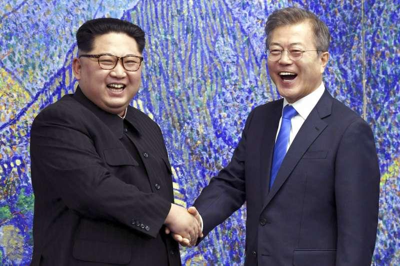 金正恩與文在寅在和平之家的金剛山畫作前握手。(美聯社)