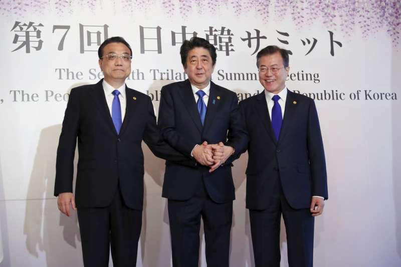 中日韓領導人會議9日在東京召開,安倍晉三、文在寅、李克強三人握手合影。(美聯社)