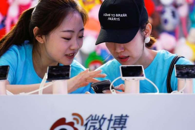 2018年4月27日,在北京舉行的全國移動互聯網大會(GMIC)期間,工作人員在新浪微博的攤位上使用智慧型手機。一個人的帽子上有英文,意思是「我是來讓人心碎的」。