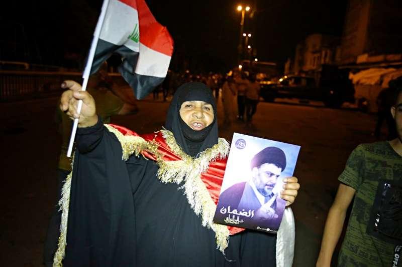 2018年5月14日,支持薩德爾的民眾湧入伊拉克首都巴格達,手舉薩德爾肖像,慶祝薩德爾的「向改革前進」聯盟成為國會第1大聯盟。(AP)