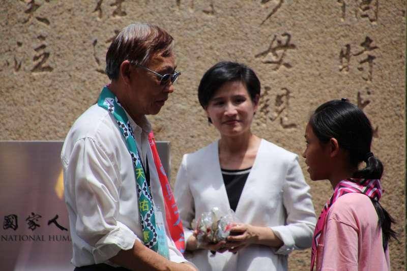 國家人權博物館今(17)在綠島園區舉行揭牌儀式,政治受難者前輩陳欽生(左)將人權彩飄親手掛在綠島公館國小學童身上。(文化部提供)