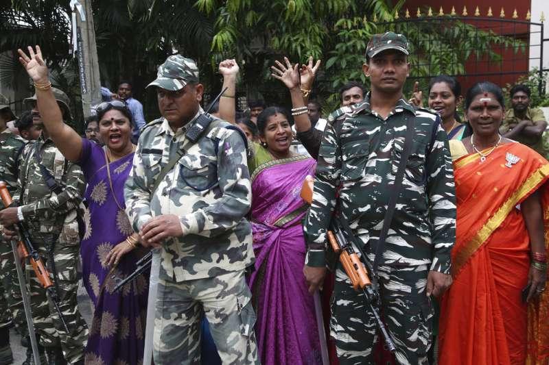 2018年5月15日,印度卡納塔克邦舉行議會選舉之後,民眾在軍人旁慶祝印度人民黨取得領先。(AP)
