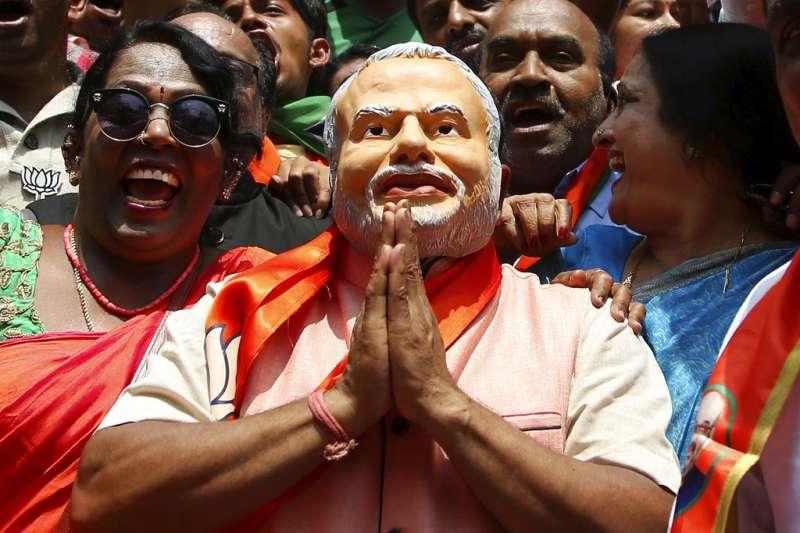 2018年5月15日,印度卡納塔克邦議會選舉之後,民眾頭戴印度總理莫迪的面具,慶祝印度人民黨取得領先。(AP)