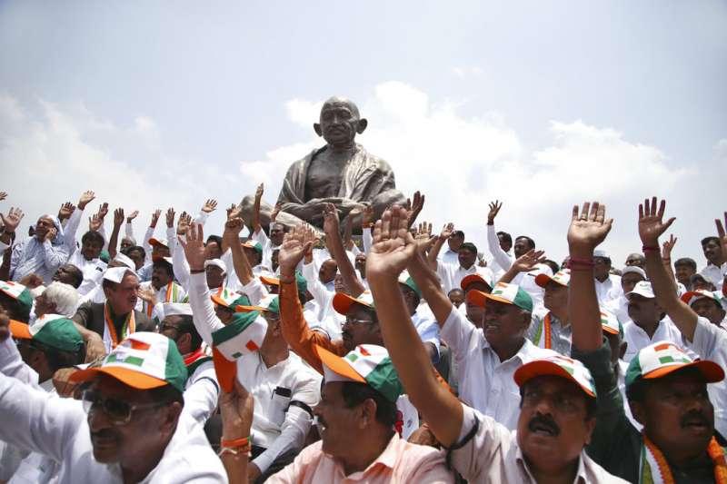 2018年5月17日,印度卡納塔克邦議會選舉之後,印度國大黨的支持者在聖雄甘地的塑像前集會。(AP)