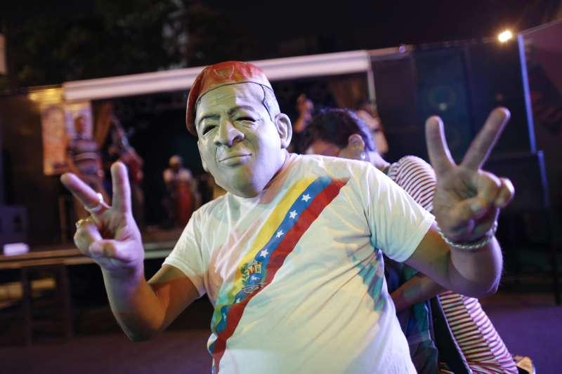 2018年委內瑞拉總統大選結果出爐,現任總統馬杜洛的支持者戴著前任總統查維茲的面具比出勝利手勢(AP)