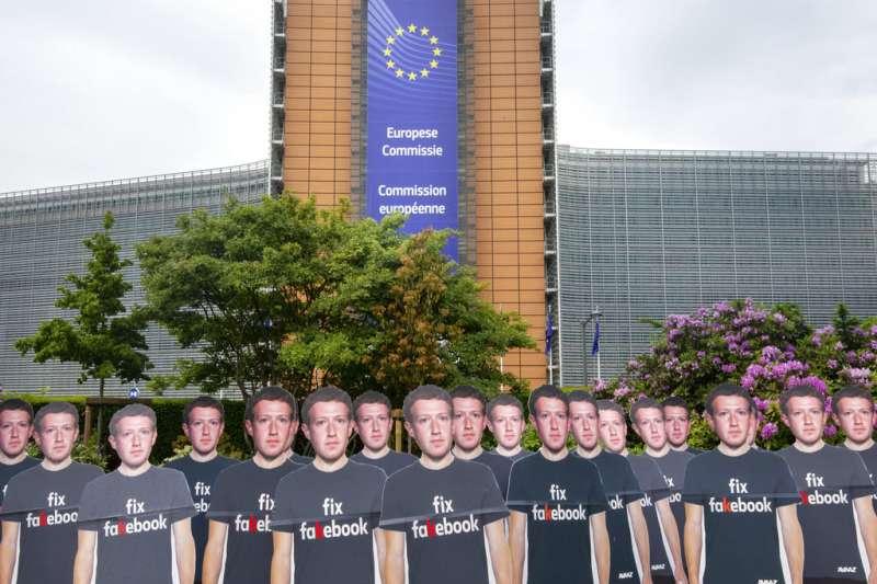 2018年5月22日,臉書執行長祖克柏出席歐洲議會聽證會,場外出現抗議立牌。(AP)