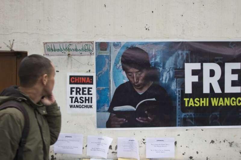 印度達蘭薩拉的一名西藏流亡者走過一面要求釋放扎西文色的橫幅海報。(美聯社)