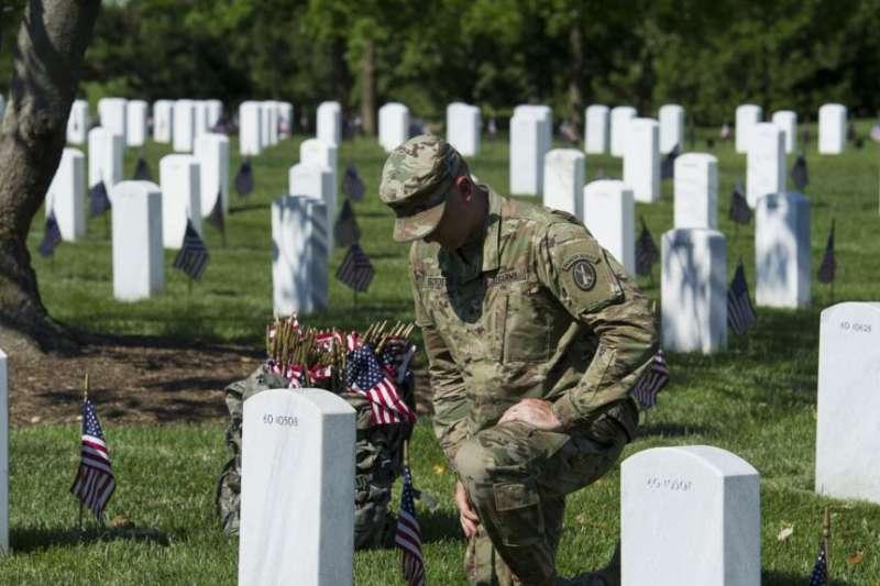 在華盛頓郊區的阿靈頓國家公墓,號稱老衛隊的美國陸軍第三步兵團的一位軍人把小型國旗插在每一座墓碑前,他短暫停下來,悼念一名陣亡者。(美聯社)