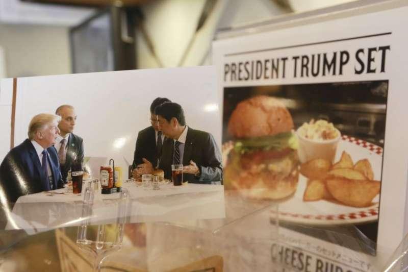 美國總統川普以喜愛速食聞名,2017年11月5日訪問日本時,日本首相安倍晉三也請他吃漢堡。(美聯社)