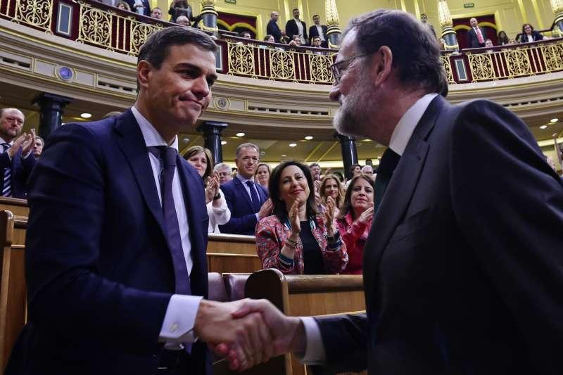 西班牙眾議院1日不信任案投票結果出爐,確定下台的拉霍伊(右)與接任總理的桑切斯(左)握手(美聯社)