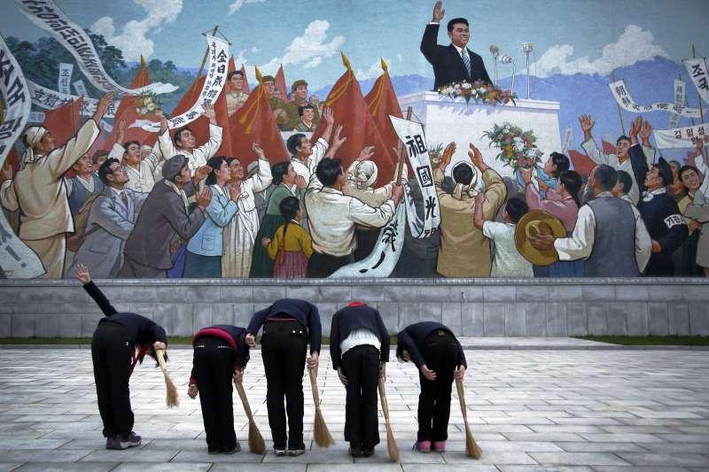 北韓民眾對著牆上領導人的畫像敬禮。(美聯社)