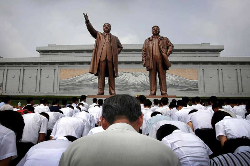 北韓民眾對著金正日與金日成的雕像鞠躬敬禮。(AP)