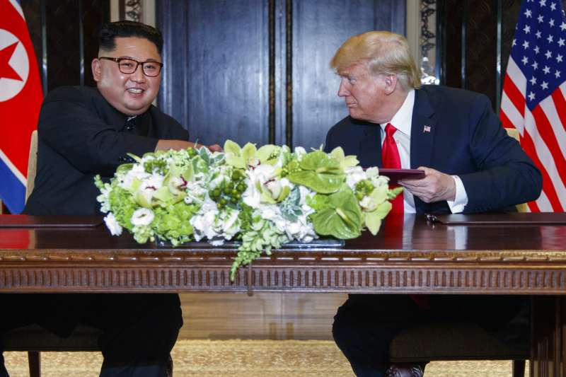 川普、金正恩簽署聯合聲明之後,微笑握手致意。(AP)