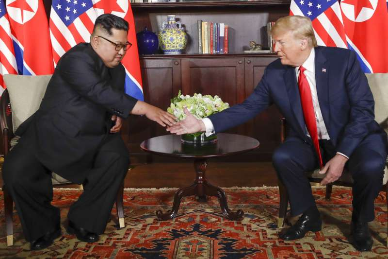 川普、金正恩一對一會談前握手致意。(AP)