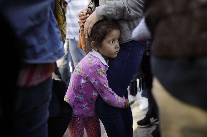 小女孩妮可緊抱著母親大腿,她們來自墨西哥南部格雷羅州,為了逃離家鄉的黑幫暴力,於是來到美墨邊境等待,希望能獲得美國的政治庇護(美聯社)