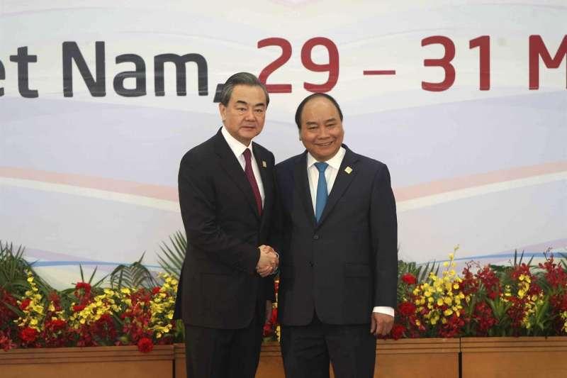 第八屆湄公河經濟合作戰略峰會中,越南總理阮春福(右)與中國外交部長王毅(左)握手。(美聯社)