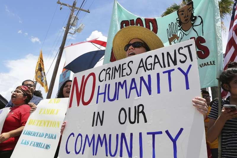 美國民眾拿著標語「我們社區容不下違反人權的罪」,抗議川普的「零容忍」移民政策。(美聯社)