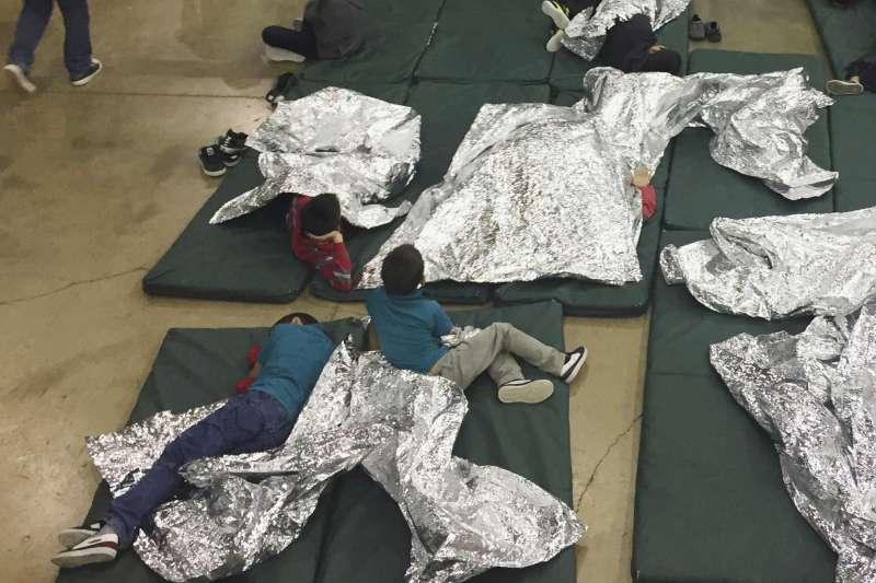 美國德州南部邊境城市麥卡倫的處置中心內,孩童被關在籠子裡,睡在地板上,蓋著鋁箔毯(美聯社)