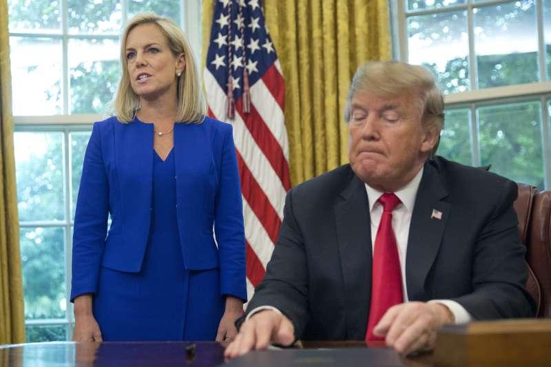 2018年6月20日,美國總統川普在白宮簽署行政命令,改變遭到各方譴責的「拆散家庭」移民政策,左為國土安全部長尼爾森(AP)