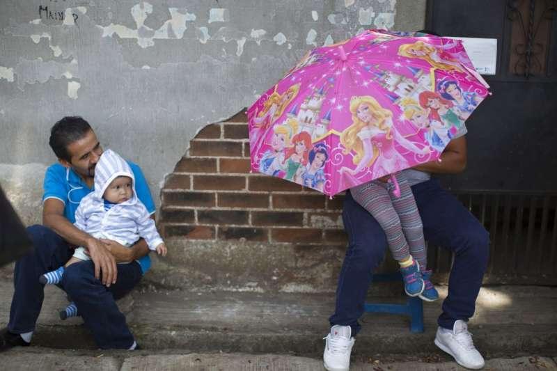2018年6月20日,民眾在瓜地馬拉空軍基地外,等待遭到美國遣返的親友。(AP)
