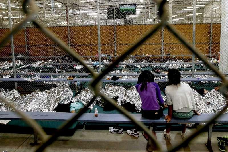 6月18日,美國亞利桑那州一間非法移民兒童安置中心內,兩名女童正在看電視上的世界盃足球賽。這些非法移民兒童被迫與父母分開後,被關在籠子裡(美聯社)